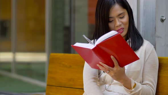 Thumbnail for Smiling Asian Woman Reading Book Sitting on Bench