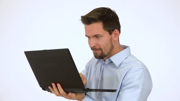 Thumbnail for A Young Handsome Man Looks Mischievously Around and Works on a Computer - White Screen Studio