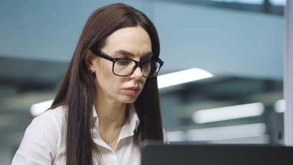 Businesswoman in Eyeglasses Reading Information on Laptop