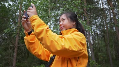 Asian woman taking a photo of view in the forest