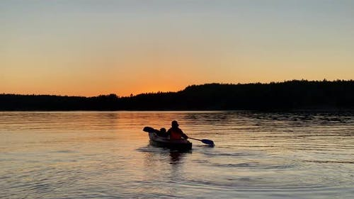 Silhouette of Person Rowing Kayak Along Tranquil Lake
