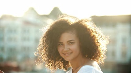 A Young Attractive Woman Playing with Her Curly Hair and Performing Sexy Dancing on an Urban