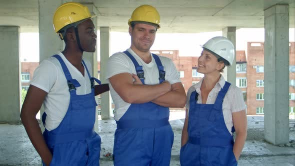 Thumbnail for Confident Diverse Team of Workmen and Women Standing Grouped in Their Dungarees and Hardhats