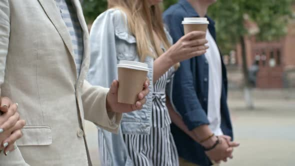 Two Couples Walking with Coffee Cups