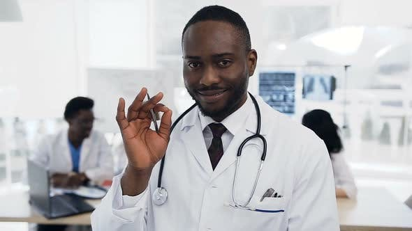 Thumbnail for African Doctor Looking to the Camera with Team of Cowoker