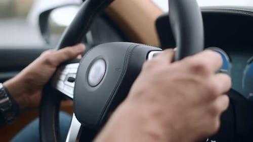 Closeup Male Putting Hands on Steering Wheel. Man Holding Steering Wheel at Car