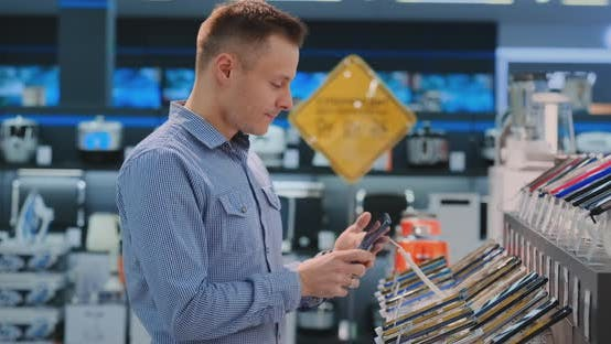 Cover Image for Young Handsome Man in Blue Shirt Chooses a New Mobile Phone in an Electronics Store. Modern