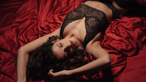 Verführerische Mädchen berühren sich selbst Seide Bett. Erotische Frau posiert auf Satinblätter