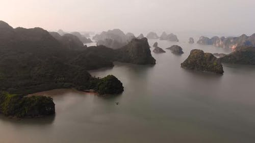 Aerial: flying over Ha Long Bay rock pinnacles at sunset, famous tourism destination in Vietnam