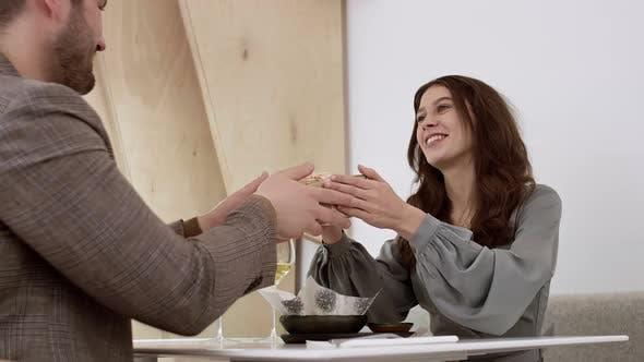 Man Receiving Present from Girlfriend in Restaurant