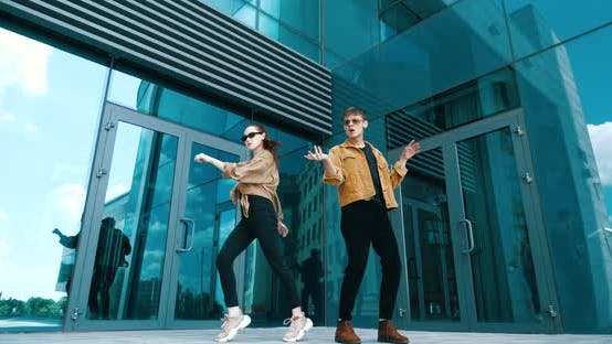 Stylish Brother and Sister Spend Time Together Outside, Dancing Modern Choreography. Two Models