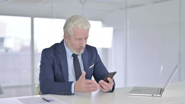 Upset Old Businessman Reacting To Failure on Smartphone