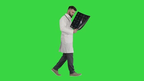 Doctor From Middle East Walking and Looking at Ct Scan on a Green Screen, Chroma Key.