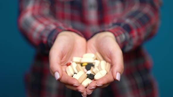 Thumbnail for Frau präsentiert eine Handvoll Pillen