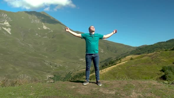 Thumbnail for A Young Man Stands in a Dress with Him Arms Raised Up Against the Backdrop of Mountains. The Sun