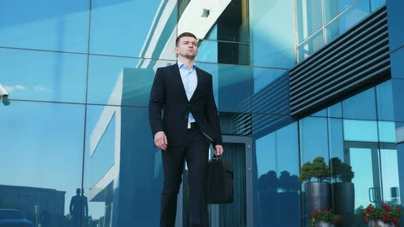 Thumbnail for Young Businessman with a Briefcase Walking in City Street Near Modern Office Building. Confident Guy