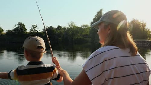 Happy Mother Teaches Little Son To Fish