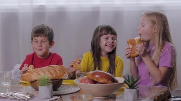 Thumbnail for Sorglose Kindheit, Happy Boy und lächelnde Mädchen sitzen an Sweet Table Essen aromatisches Gebäck