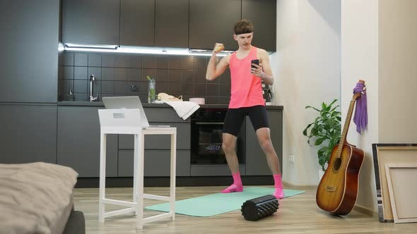 Funny sexy guy in pink top typing messages on cellphone and doing sports exercises