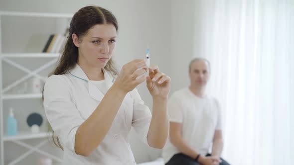 Thumbnail for Young Beautiful Woman with Syringe Standing in Hospital Ward with Blurred Stressed Man at the