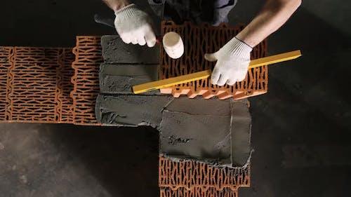 Baumeister korrigiert Ziegel während des Mauerwerks