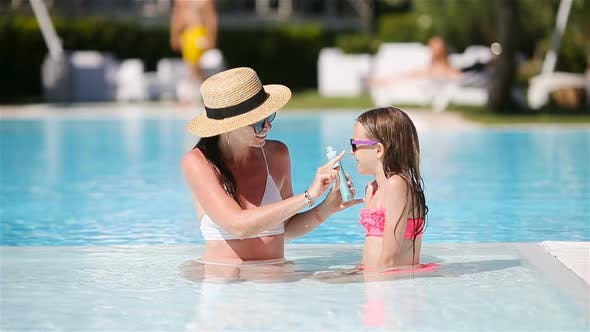 Thumbnail for Young Mother Applying Sun Cream To Daughter Nose