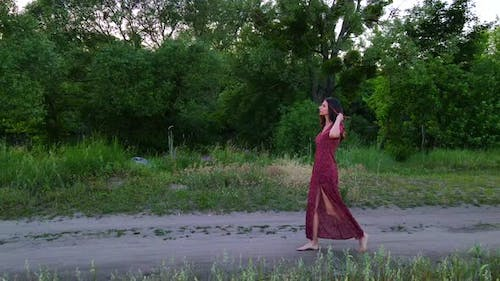 Young Woman with Long Hair in Long Dress Walks on a Field Road, Slow Motion  Shot