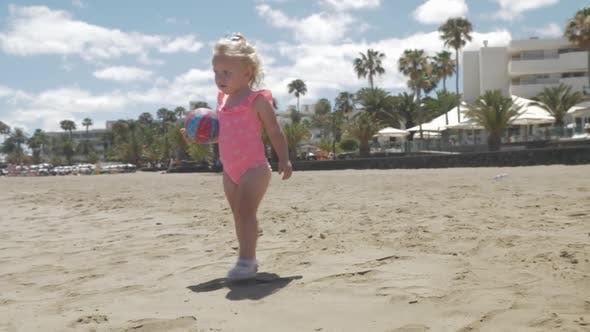 Cover Image for Cute Baby Girl in Pink Swimsuit Walking on the Beach