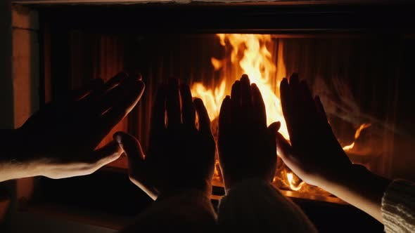 Thumbnail for Hands of a Man and a Woman Bask in Front of a Fire in a Fireplace