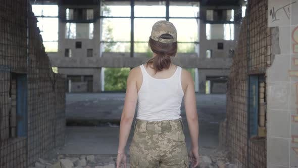 Thumbnail for Attractive Young Woman in Military Uniform Walking Slowly in Dusty Dirty Abandoned Building