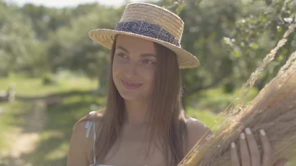 Attractive Young Woman in Straw Hat and Long White Dress Looking at the Camera Smiling Standing in