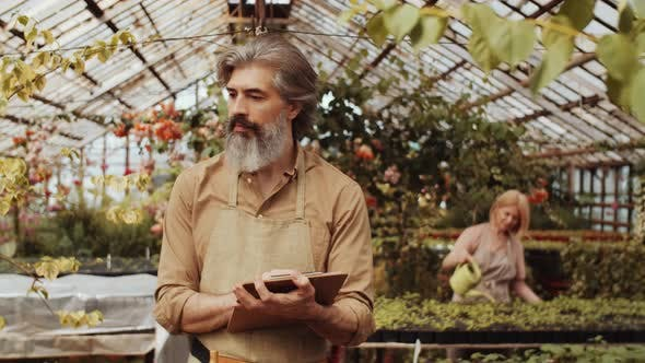 Thumbnail for Senior Farmer Going though Greenhouse and Writing on Clipboard
