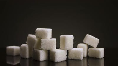 A pile of sugar pieces against black background