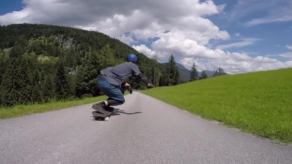 Thumbnail for A skateboarder downhill skateboarding racing on a mountain road
