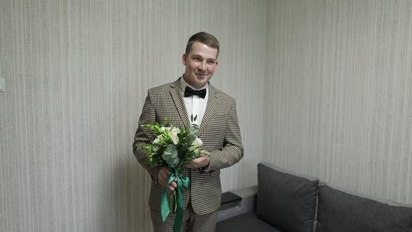 Thumbnail for Bräutigam mit Hochzeitsstrauß in seinen Händen zu Hause. Weißes Hemd, Jacke
