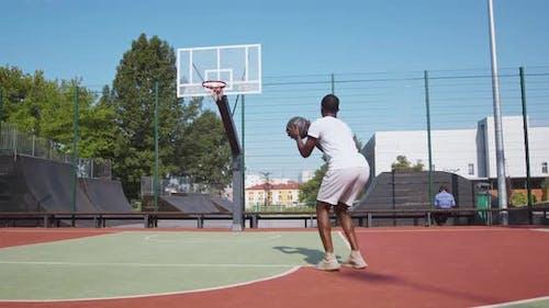 Professioneller schwarzer Streetball-Spieler wirft Ball in Basketballkorb auf Platz im Freien