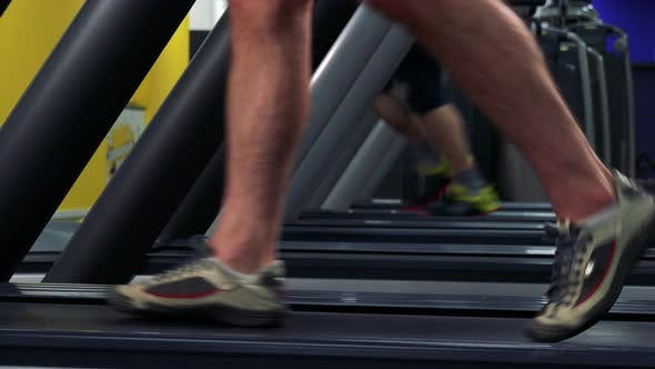 Thumbnail for A Fit Man Walks on a Treadmill in a Gym - Side Closeup on the Feet