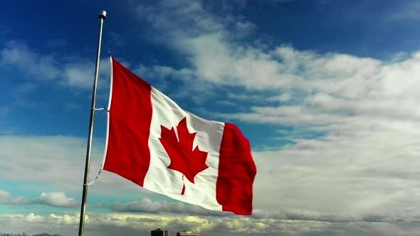 Aerial orbit of the Canada Flag on blue sky