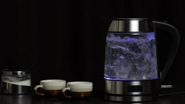 Thumbnail for Boiling Water in Glass Transparent Electric Kettle with Blue Light Illumination. Black Background