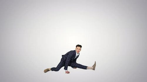 Young Attractive Male Dancer in the Strict Business Suit Dancing Making a Split on Gradient