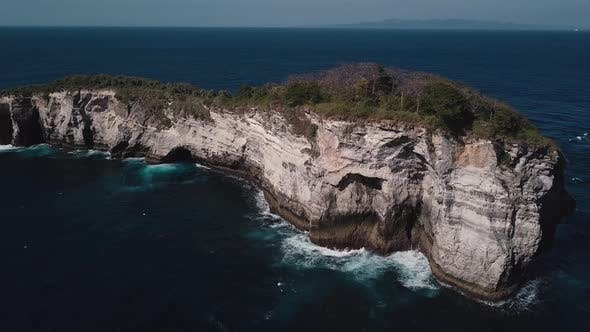 Aerial Shot of Waves Crashing on Small Tropical Rocky Island on the Coast
