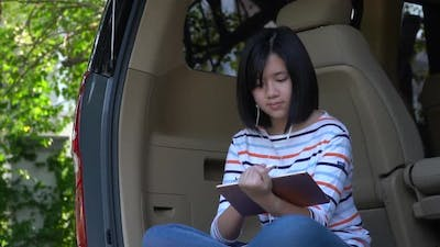 Asian Teen Using Tablet On A Car Slow Motion