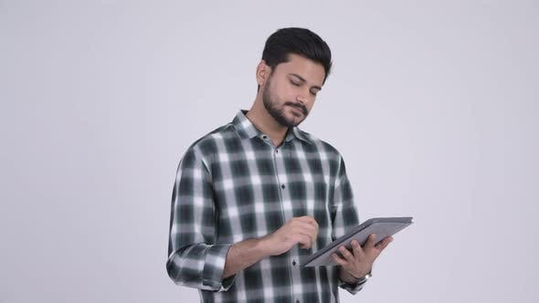 Thumbnail for Portrait of Young Happy Bearded Indian Man Using Digital Tablet