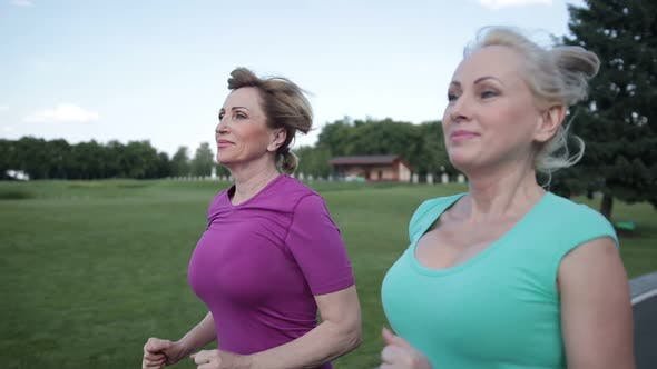 Thumbnail for Two Pretty Senior Females Joggers Training in Park