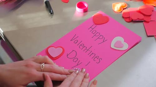 A Female Creating A Happy Valentines Day Card With Red Hearts 2