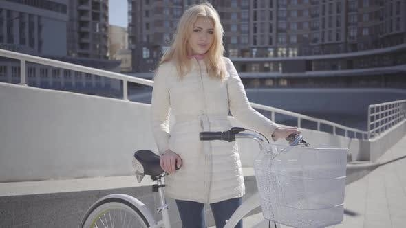 Thumbnail for Pretty Blond Smiling Woman in Warm White Jacket Standing at the City Street with Bicycle Looking in