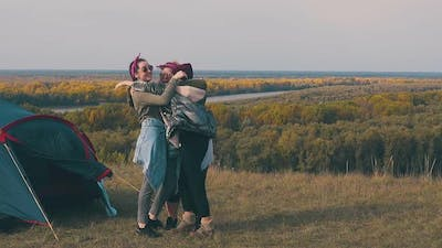 Plump Young Woman Hugs Friends with Laughter in Campsite