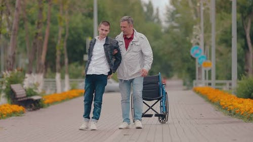 Guy with Disabilities Comes with the Support of His Father