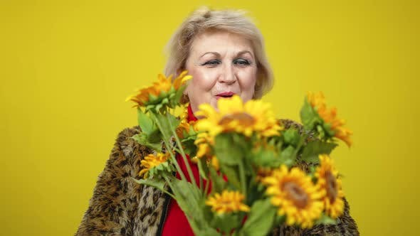 Thumbnail for Excited Senior Woman Holding Bouquet of Sunflowers and Smiling Looking at Camera