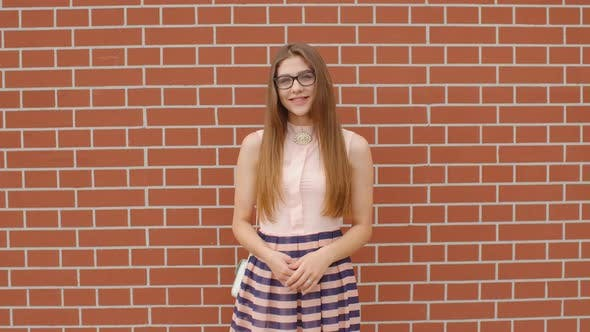 Thumbnail for Girl Student in Glasses Laughs Against a Brick Wall Background